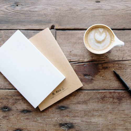 coffee cup and notebook on table