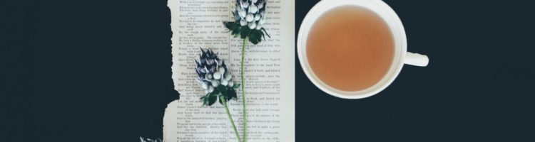 Cup of tea with book page and flowers.