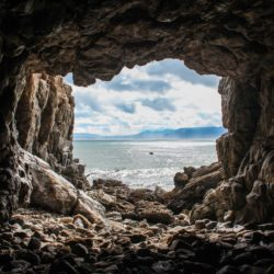 Cave with ocean in distance.
