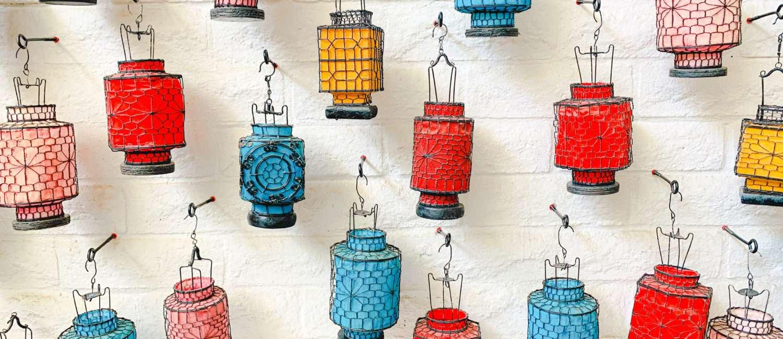 Colorful lanterns on white brick wall.