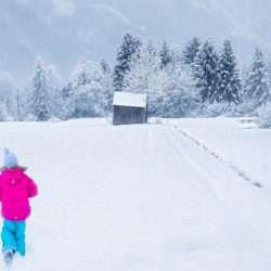 Child in pink jacket walking in snow toward cabin.
