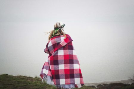 Woman wrapped in plaid blanket