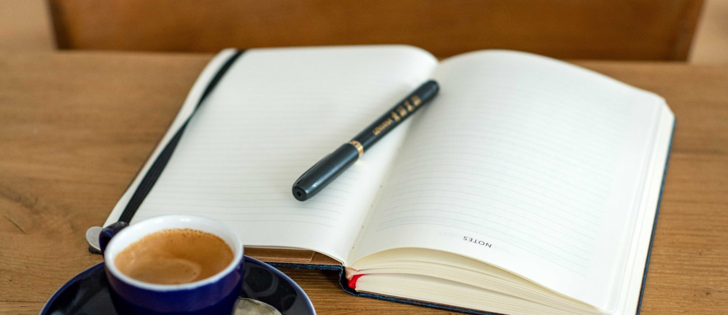 book with pen and coffee cup