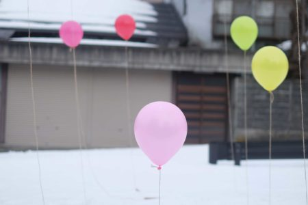 Balloons outside house in the snow